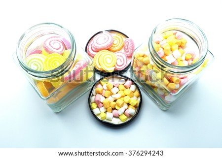 Colorful spiral jelly and colorful marshmallows with glass jars on blue-white background. Focus on jelly and marshmallows on floor.   Space for texts. - stock photo