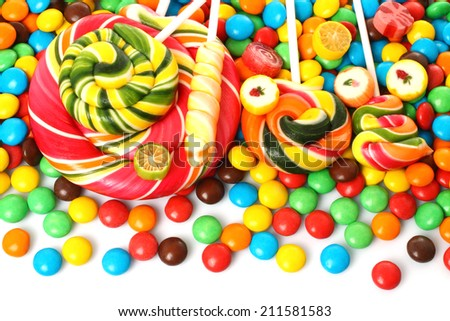 Colorful spiral lollipop with chocolate coated candy on white background   - stock photo