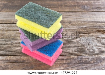 Colorful sponges on wooden background - stock photo
