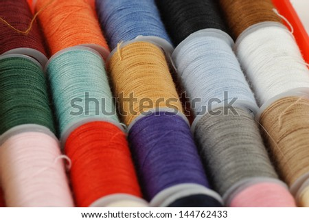 colorful spools of multi colored threads for sewing and knitting - stock photo