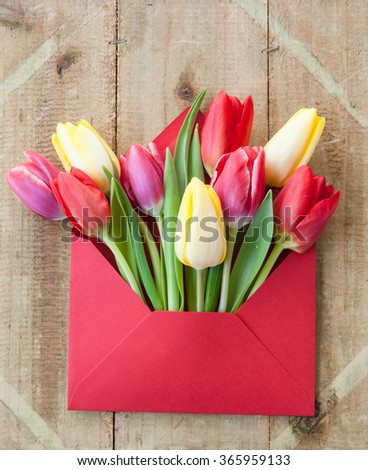 Colorful spring flowers in envelope, flower delivery concept - stock photo