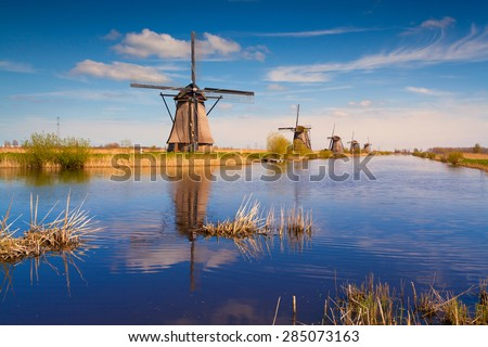 Colorful spring morning on the canal in Netherlands. Dutch windmills at Kinderdijk, an UNESCO world heritage site. - stock photo