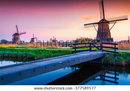Colorful spring scene in the famous Kinderdijk canals with windmills, UNESCO world heritage site. Sunset in Dutch village Kinderdijk, Netherlands, Europe. - stock photo