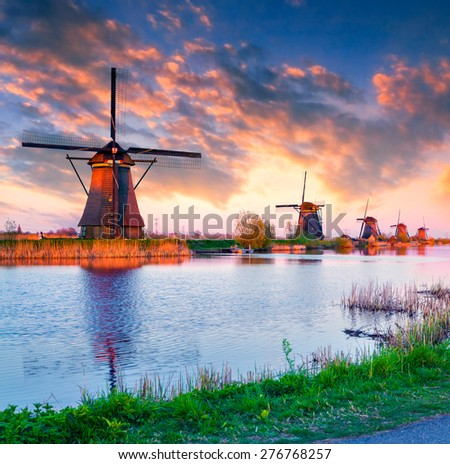 Colorful spring sunset in Netherlands. Dutch windmills at Kinderdijk, an UNESCO world heritage site. - stock photo