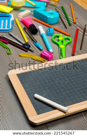 Colorful stationery on the floor moving towards a small blackboard with chalk. - stock photo