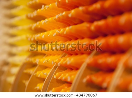 Colorful stick candles with orange and yellow tonality, arranged in shelves and sorted by color in a candle shop. - stock photo