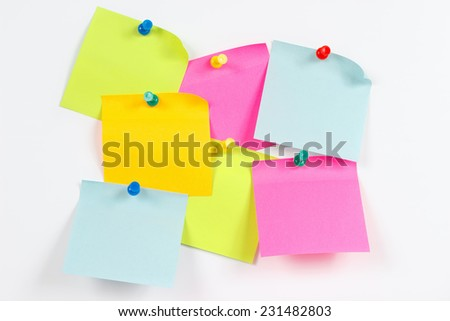 Colorful stickers on a white message board - stock photo