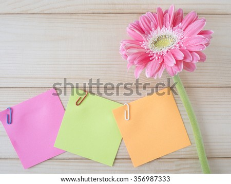 Colorful sticky note and pink flower on wood background - stock photo