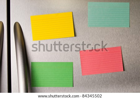 Colorful sticky notes on a stainless steel refrigerator. - stock photo