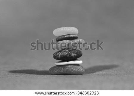Colorful stones in a pile. This demonstrates nicely about the importance of teamwork. Every single individual is important for the whole team. Image is in black and white. - stock photo
