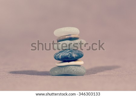 Colorful stones in a pile. This demonstrates nicely about the importance of teamwork. Every single individual is important for the whole team. Image has a vintage effect applied and has room for tex - stock photo