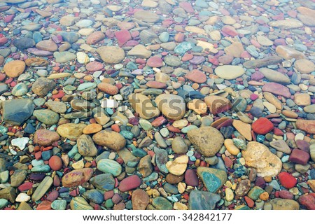 Colorful stones under the clear water of Lake McDonald. Glacier National Park, Montana - stock photo