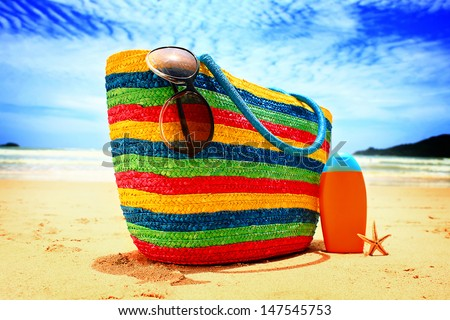 Colorful straw bag, sunglasses, bottle of sun lotion and starfish on paradise tropical beach - stock photo