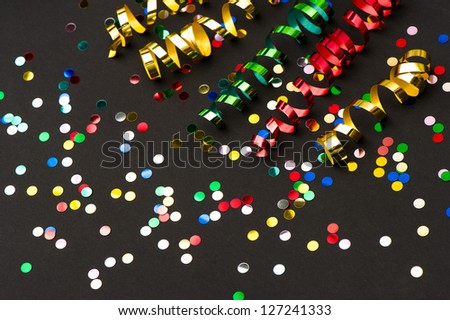 colorful streamer and confetti on black paper background. party decoration - stock photo