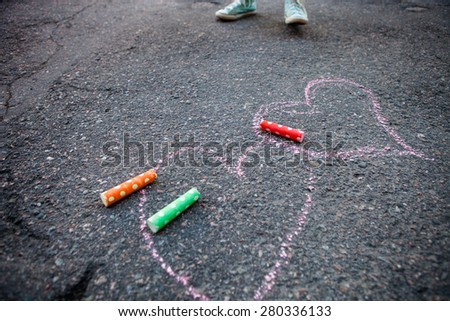 Colorful street chalk on asphalt with hearts drawn to the ground - stock photo