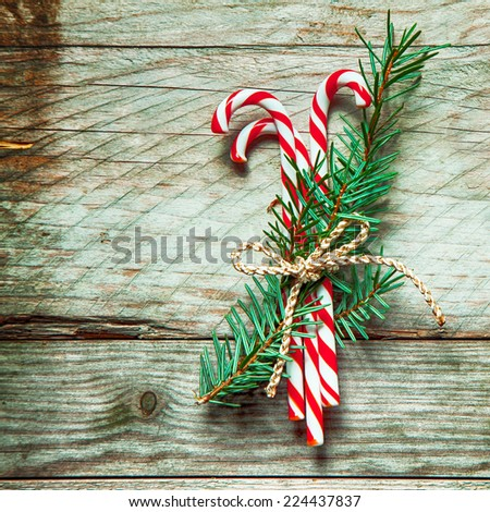 Colorful striped red and white Christmas candy canes tied in a bundle with sprigs of pine with string on a rustic wooden background, square format with copyspace - stock photo