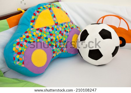 Colorful stuffed toys in a baby boy crib, car and football ball - stock photo
