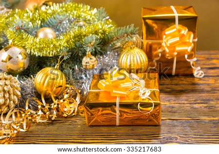 Colorful stylish gold Christmas still life with two gifts in gold foil alongside a fir branch decorated with baubles and tinsel on a textured wood table - stock photo