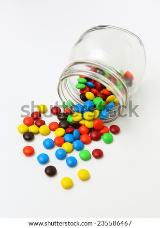 Colorful sugar-coated chocolate smarties in a glass jar on a white background - stock photo