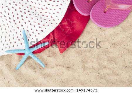 Colorful summer beachwear, flip flops, towel, hat, sunglasses and starfish on sand beach. - stock photo