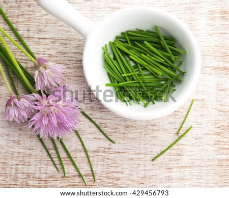 colorful summer chopped chives in a white dish with purple flowers, window lit for soft focus,  wood grain background. - stock photo