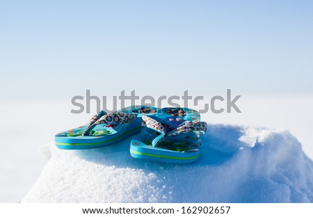Colorful summer flip-flops on snow - stock photo