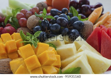 Colorful summer fruit platter with mango, pineapple, watermelon, grapes, cherries, apricots, strawberries, cantaloupe, walnuts and mint - stock photo