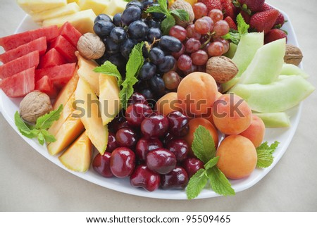 Colorful summer fruit platter with pineapple, watermelon, cherries, apricots, strawberries, cantaloupe, walnuts and mint - stock photo