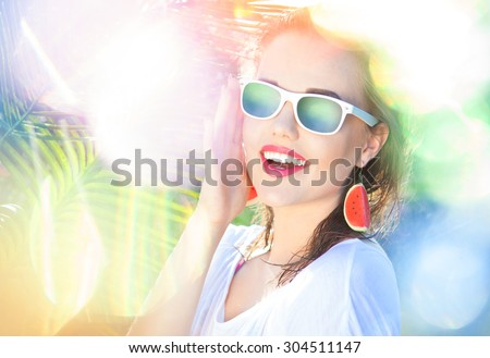 Colorful summer portrait of happy young attractive woman wearing sunglasses and watermelon earrings, beauty and fashion concept natural bokeh and light effect - stock photo