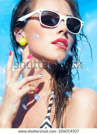 Colorful summer portrait of young attractive brunette woman wearing sunglasses at the swimming pool  - stock photo