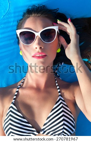 Colorful summer portrait of young attractive brunette woman wearing sunglasses lying down at the swimming pool - stock photo