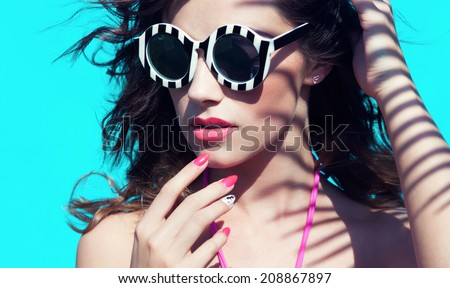 Colorful summer portrait of young attractive brunette woman wearing sunglasses under a palm tree by the swimming pool  - stock photo