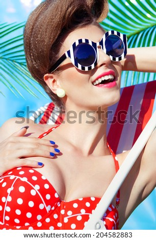 Colorful summer portrait of young attractive woman wearing bikini and sunglasses lying down under a palm tree by the swimming pool  - stock photo