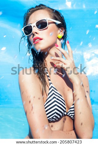 Colorful summer portrait of young attractive woman wearing sunglasses by the swimming pool  - stock photo