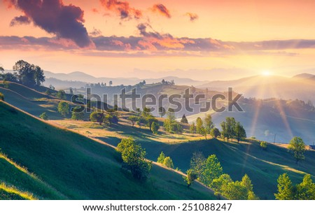 Colorful summer sunrise in the Carpathian mountains with rolling hills and valleys in golden morning light - stock photo