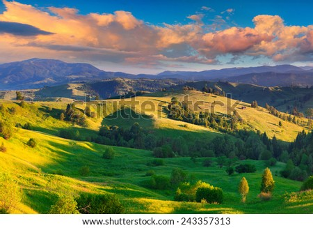 Colorful summer sunrise in the Carpathian village with rolling hills and valleys in golden morning light - stock photo