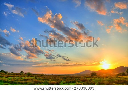 Colorful Summer sunset with sun rays coloring the clouds - stock photo
