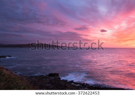 Colorful sunrise at ocean shore, Southland, New Zealand - stock photo