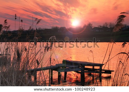 Colorful sunrise on the river with fishing bridge - stock photo