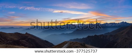 Colorful sunset behind majestic mountain peaks of the Italian Alps. Fog and mist covering the valleys below, autumnal landscape, cold feeling. Stunning sky. XXXL expansive panorama. - stock photo