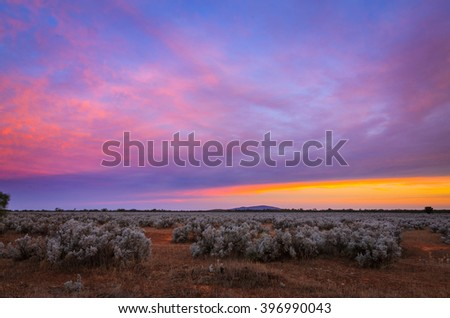 Colorful sunset in Australian remote plain rural land - stock photo