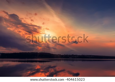 Colorful sunset majestic lake. sunlight breaks through the clouds.  dramatic scene. color in nature - stock photo