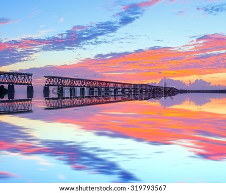 Colorful sunset over the old railroad bridge in Bahia Honda, Florida Keys with reflections  - stock photo