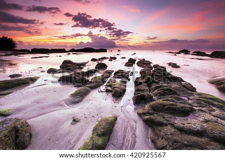 colorful sunset seascape with leading line rock at Terongkongan Beach Kudat Sabah Malaysia. Image contain soft focus and blur. - stock photo