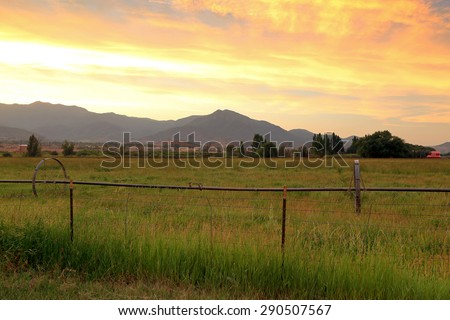 Colorful sunset sky above green fields, Utah, USA. - stock photo