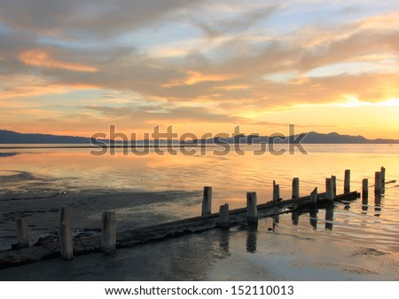 Colorful sunset sky above the Great Salt Lake with old fence posts, Utah, USA. - stock photo