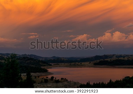 Colorful sunset sky in wilderness area. River sunset landscape viewed from lookout. Colorful orange sunset sky and river. Focus on sky, copy space - stock photo