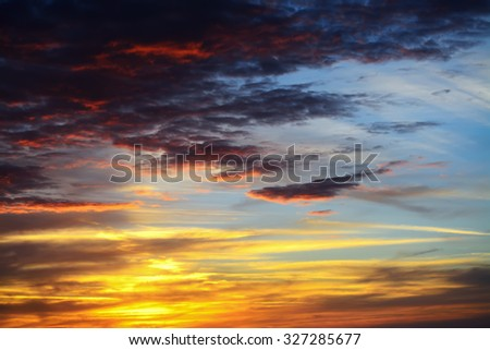 colorful sunset with dark clouds - stock photo