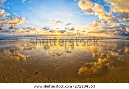 Colorful sunset with reflections at tropical beach - stock photo