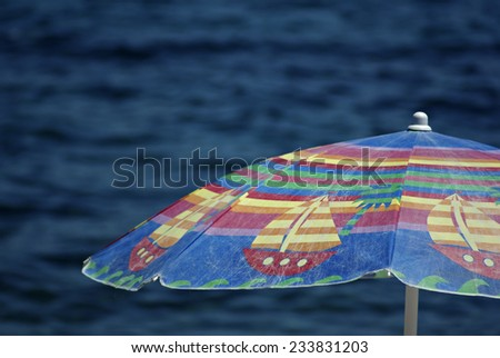 Colorful sunshade with deep blue sea in background at sunny summer day. - stock photo